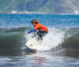 A kid surfing a wave in Madeira